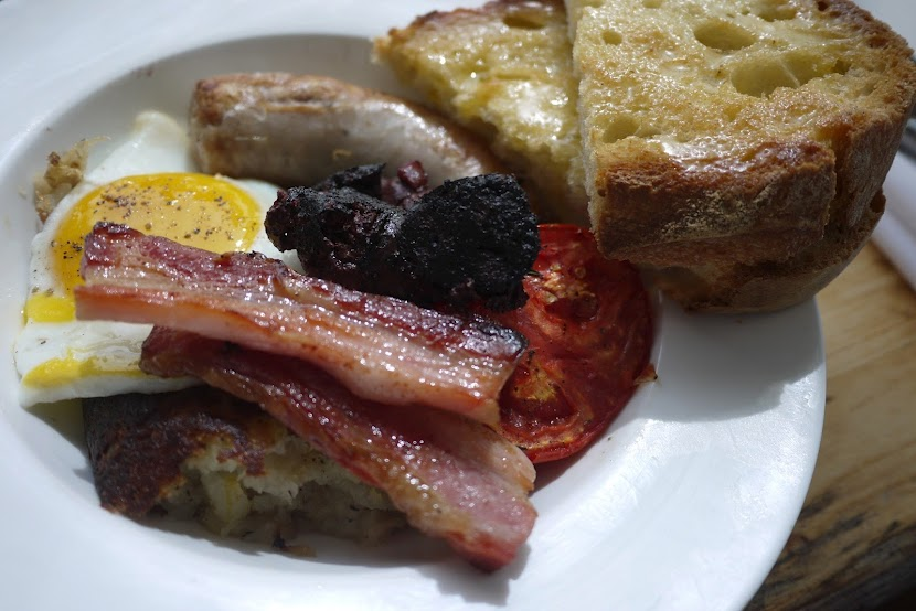 English breakfast:  sausage, bacon, blood pudding, a fried egg, grilled tomato, bubble & squeak and toast